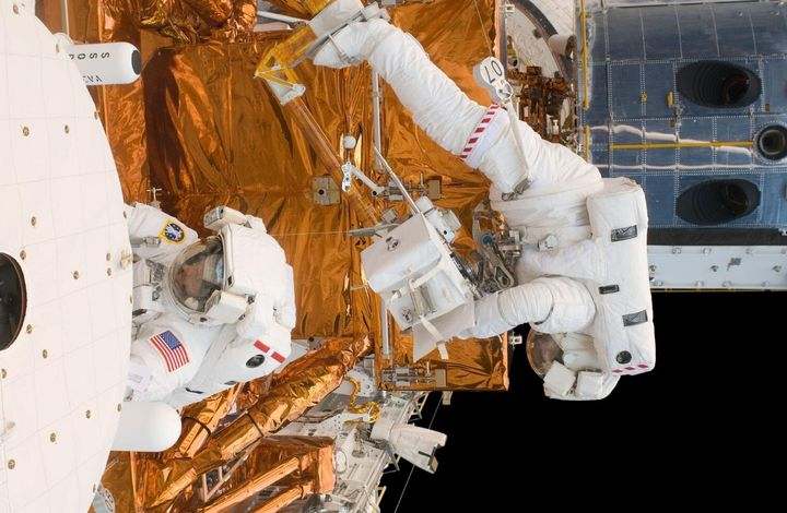 Astronauts Michael Good and Mike Massimino (l-r) work on the Hubble Space Telescope