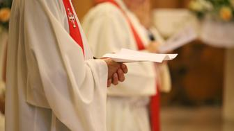 young priest with a cassock and hands joined in prayer during Holy Mass