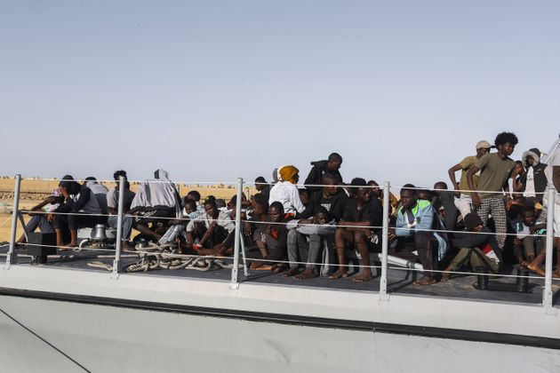 Rescued migrants sit ona coast guard boat in the city of Khoms, around 120 kilometers (75 miles) east...