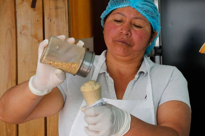 In this Sept. 28, 2019 photo, Maria del Carmen Pilapana tops a scoop of a guinea pig flavored ice cream with peanuts, at her