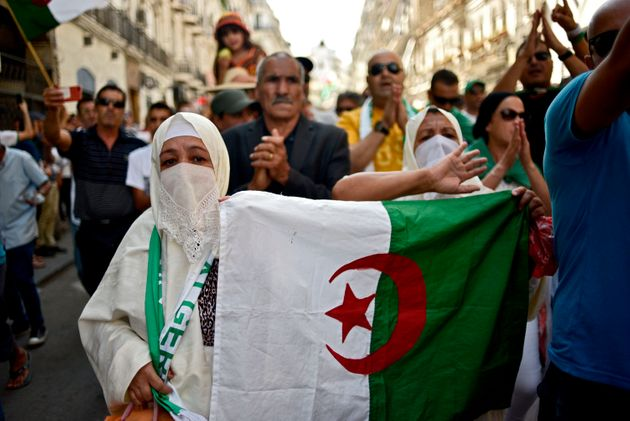 A woman wearing a hayek (traditional Algerian outfit) holds up an Algerian national flag during a demonstration...