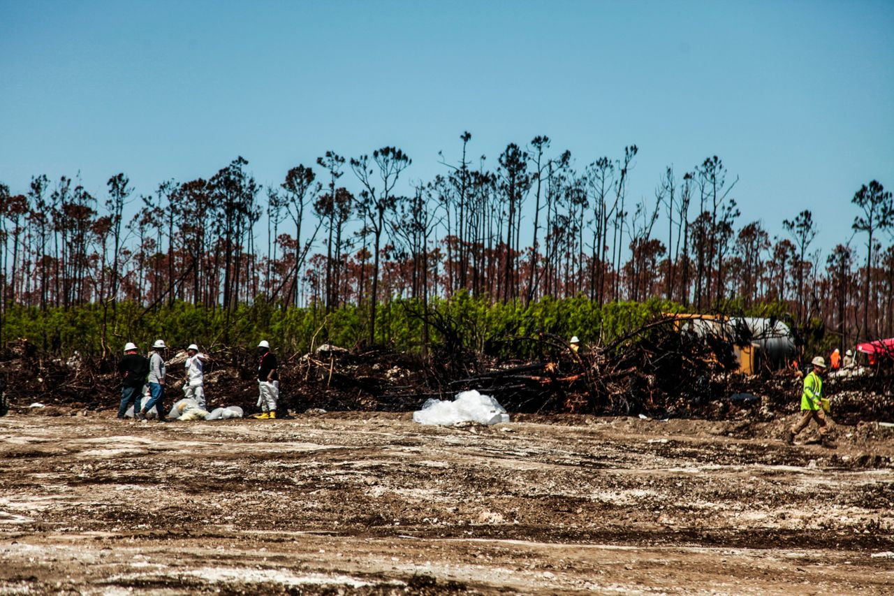 Workers clean up oil-covered debris.