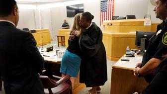 Amber Guyger leaps from her chair and gives Tammy Kemp a hug after she had given her a Bible, Guyger's 10-year prison sentence for murder at the Frank Crowley Courts Building in Dallas, Texas, U.S. October 2, 2019.  Tom Fox/Pool via REUTERS.  MANDATORY CREDIT