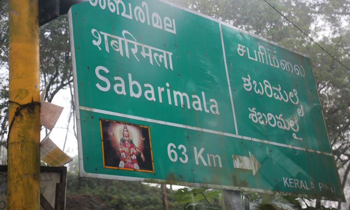 Road sign showing the distance to the Sabarimala temple in Kerala, India.