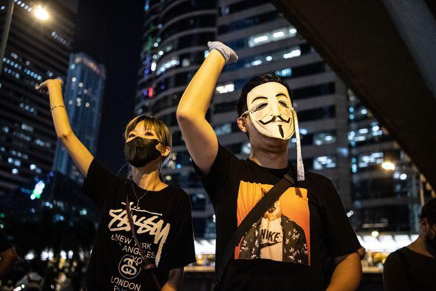 顔を隠したデモ参加者たち