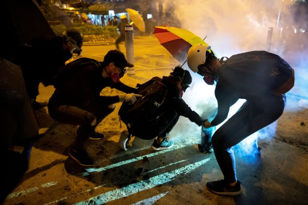 Anti-government protester takes cover from a tear gas canisters, after leader Carrie Lam announced emergency...