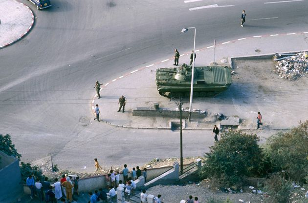 Soldiers with the Algerian armed forces patrol the streets of Algiers in military tanks after riots broke...