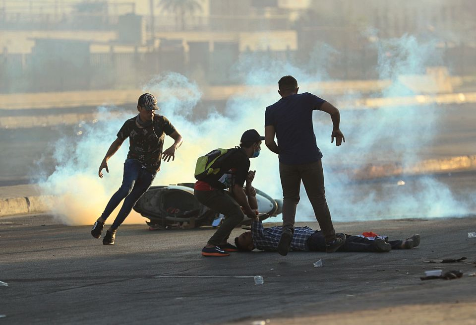 Anti-government protesters rush to an injured protestor during a demonstration in Baghdad, Iraq,