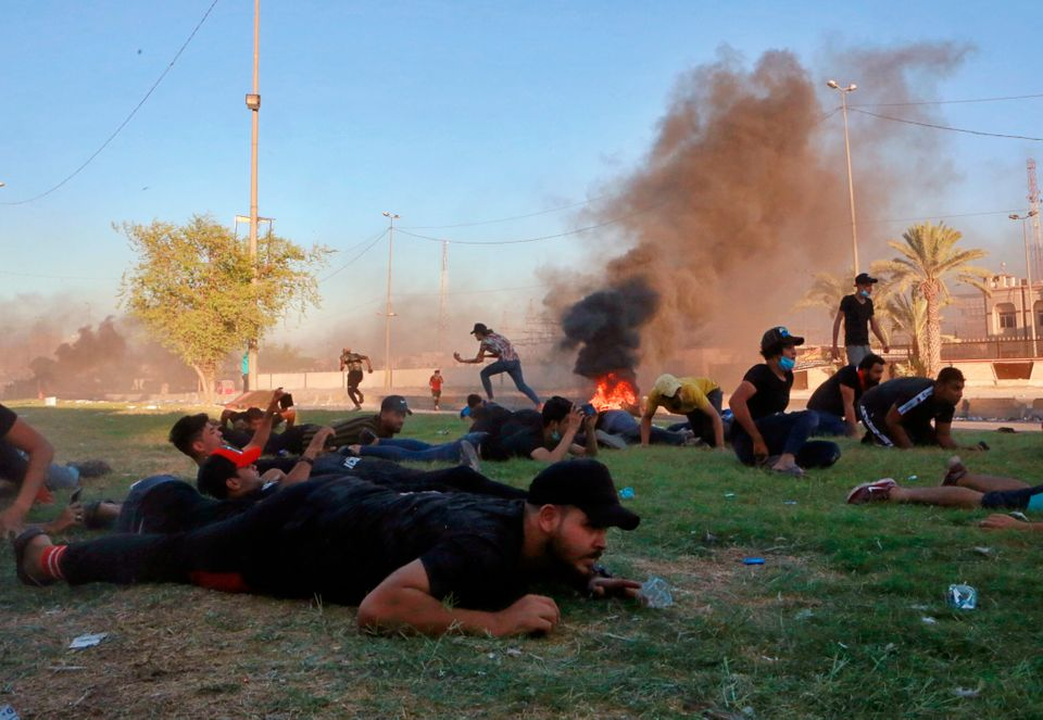 Anti-government protesters take cover while Iraq security forces fire during a demonstration in Baghdad,...