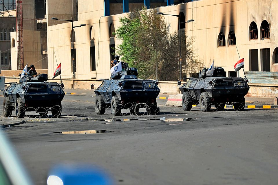 Iraqi security forces close a bridge road near the site of the protests in Tahrir square, central Baghdad,...