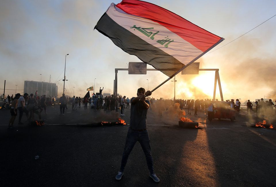 An Iraqi protester waves the national flag during a demonstration against state corruption, failing public...