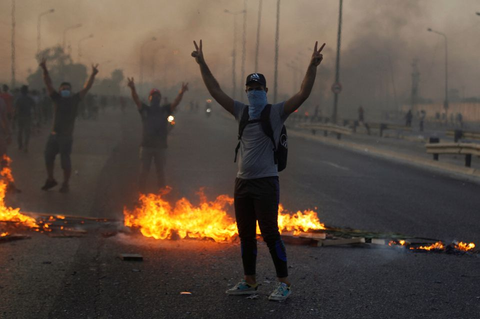 Demonstrators gesture near burning objects at a protest during a curfew, two days after the nationwide...