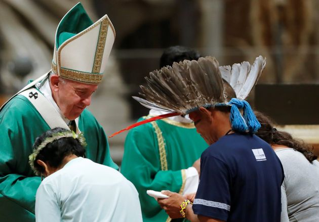 Pope Francis greets natives from the Amazonas region as he leads a Mass to open a three-week synod of...