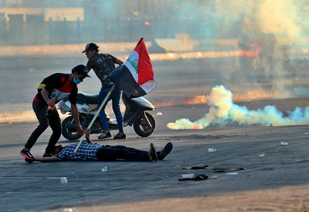 A protester falls injured while holding a national flag during a demonstration in Baghdad, Iraq, Saturday,...