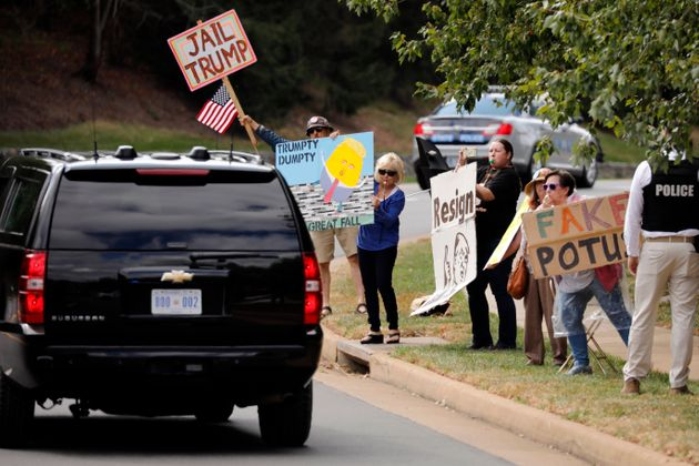 U.S. President Donald Trump's motorcade passes by protestors outside Trump National Golf Club in Sterling,...