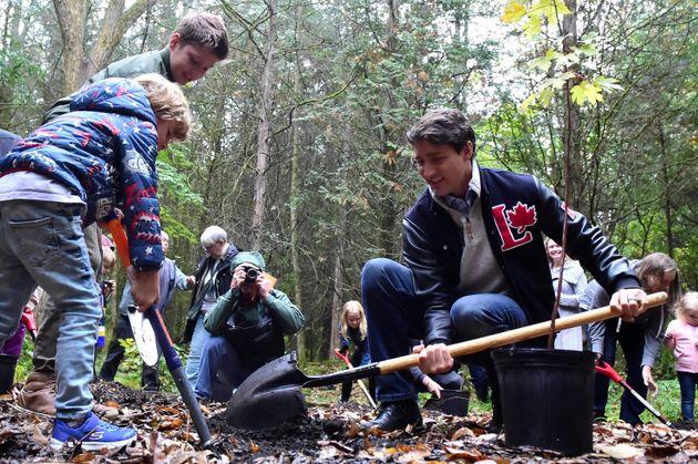 Le chef libéral Justin Trudeau plante un arbre avec ses fils Xavier et Hadrien (à gauche)...