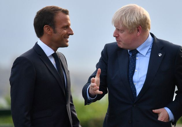 French President Emmanuel Macron speaks with Prime Minister Boris Johnson at the official welcome during...