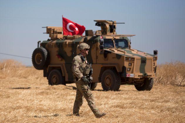 Un soldado de EEUU pasa ante un blindado turco, en una patrulla conjunta en la frontera con Siria, el...