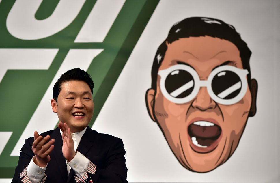South Korean singer Psy, 37, applauds during a press conference to promote his seventh album at a hotel in Seoul on November 30, 2015.