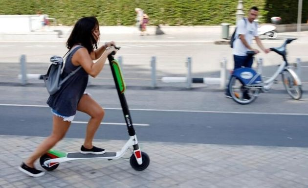 Una joven con un patinete por una acera de