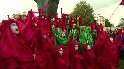 Tunica rossa e volto bianco. A Londra la protesta degli ambientalisti diventa uno show