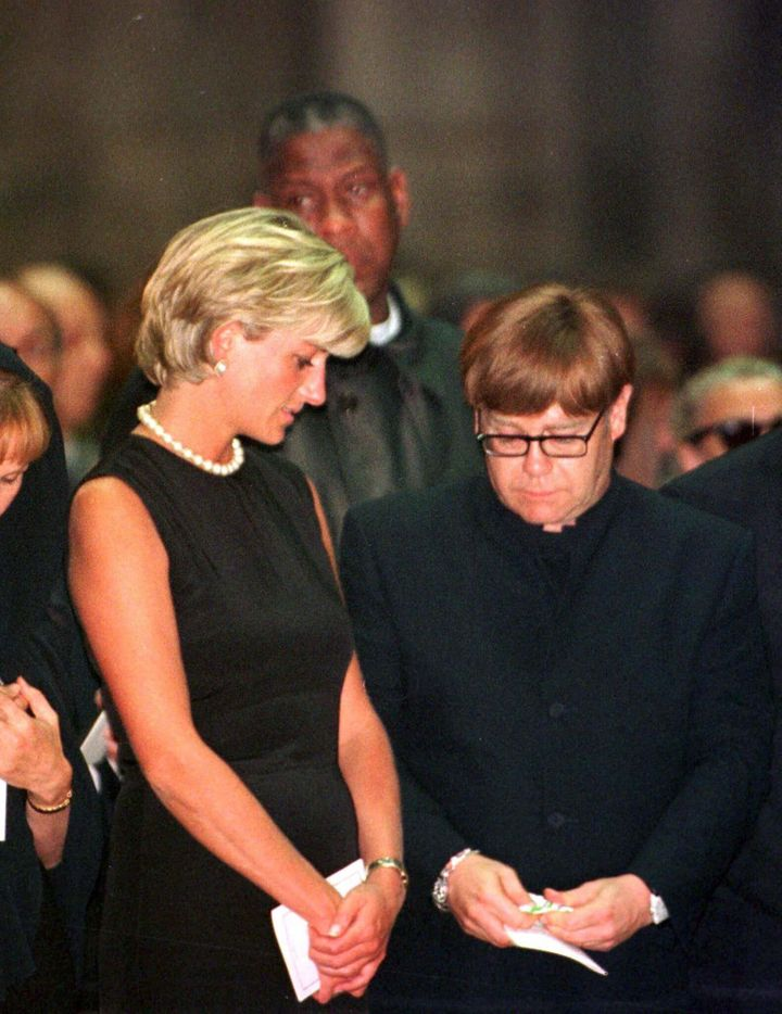 Princess Diana comforts Elton John as he weeps openly at a memorial mass for Italian fashion designer Gianni Versace in Milan