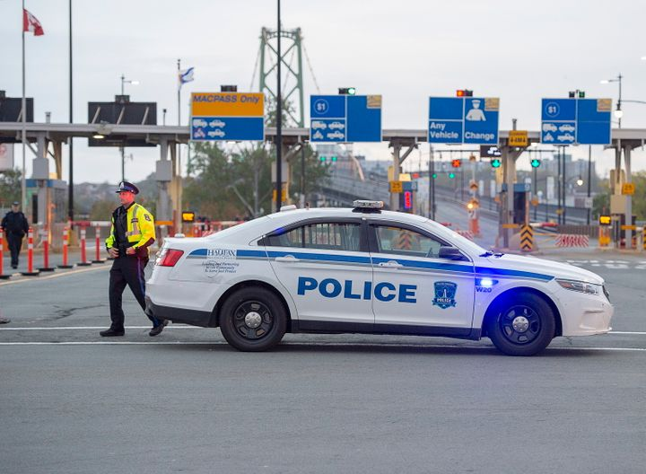 A Halifax police officer walks beside his vehicle at the Angus L. Macdonald Bridge in preparation for the climate protests planned for Monday in several Canadian cities.
