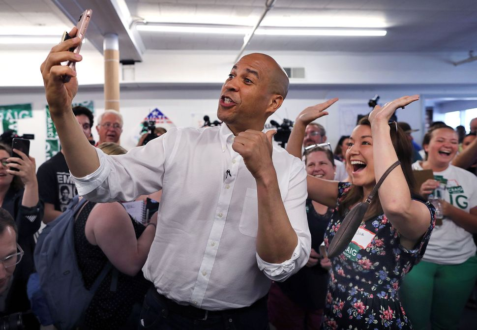 Booker records a video of himself using Celia Botto's phone as she cheers behind him during a campaign stop in Manchester, Ne