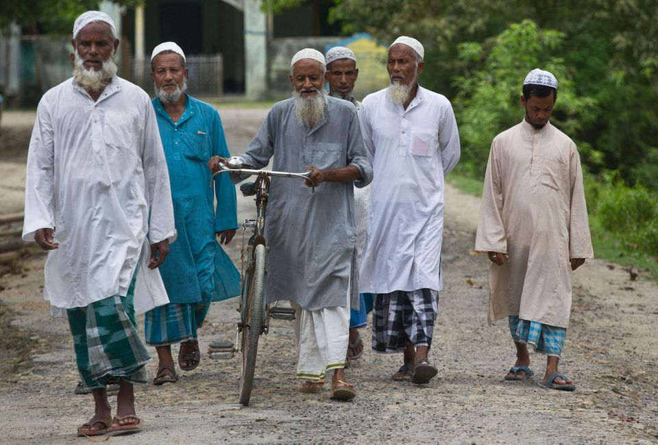 Villagers walk towards a National Register of Citizens (NRC) center to check their names on the final...