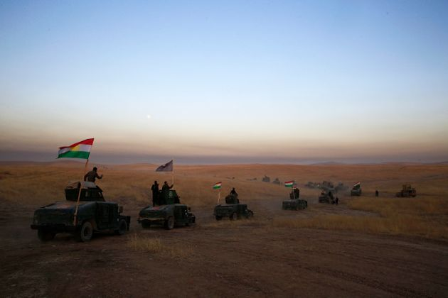 FILE -- In this Oct. 17, 2016 file photo, a Kurdish Peshmerga convoy drives towards a frontline in Khazer,...