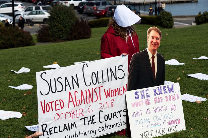 A protester in Maine holding a cut-out of Supreme Court Justice Brett Kavanaugh.