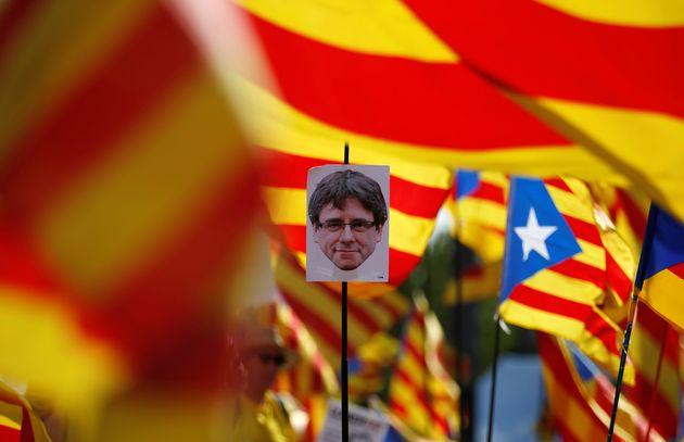 Un cartel con la cara de Puigdemont en una manifestación