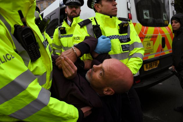 Police arrest a climate activist during an Extinction Rebellion protest in London, Monday, Oct. 7, 2019....