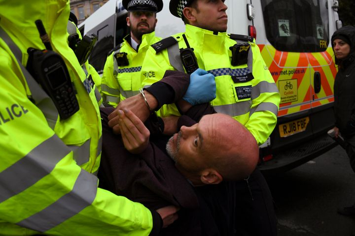 Police arrest a climate activist during an Extinction Rebellion protest in London, Monday, Oct. 7, 2019. London Police say some 135 climate activists have been arrested as the Extinction Rebellion group attempts to draw attention to global warming. Demonstrators playing steel drums marched through central London on Monday as they kicked off two weeks of activities designed to disrupt the city. (AP Photo/Alberto Pezzali)