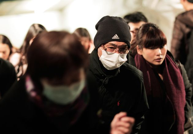 TOKYO, JAPAN - FEBRUARY 13: Commuters in Tokyo wear surgical masks to help protect themselves from the...