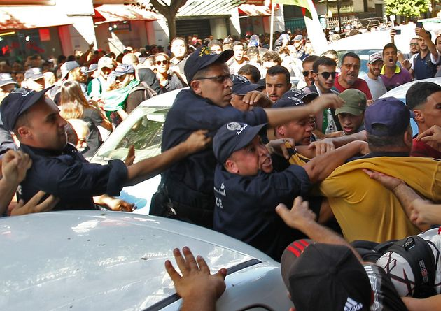 Algerian police officers clash with protesters during an anti-government demonstration in the capital...