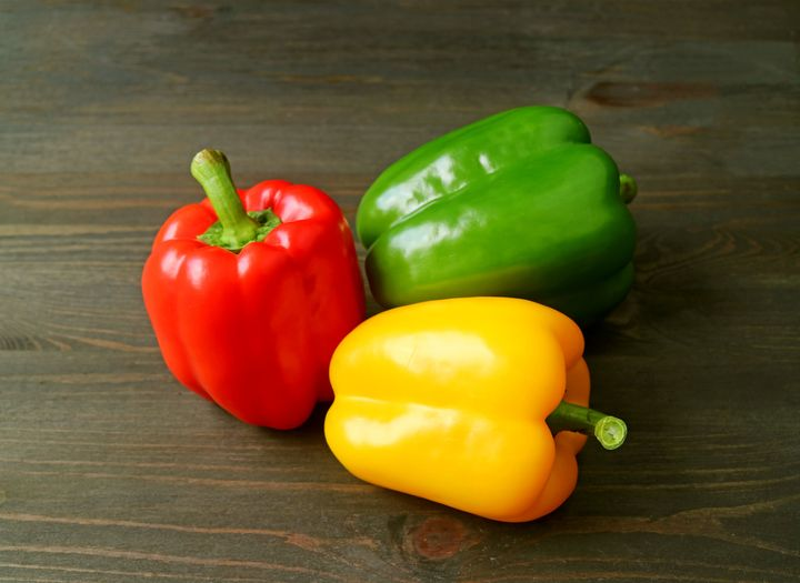 Vibrant Tricolor Bell Peppers Isolated on Dark Brown Wooden Table