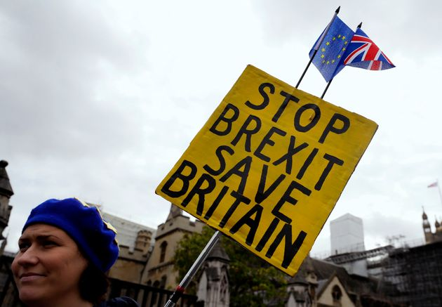 An anti-Brexit campaigner holds a banner near Parliament in London, Tuesday, Oct. 8, 2019. The British...