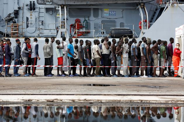 Migrants stand in line after disembarking from the Italian Navy vessel Bersagliare at the Sicilian port...