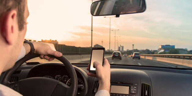 Man using cell phone while driving the car
