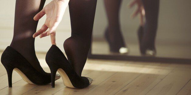 Closeup of a young woman legs wearing high heel shoes in front of mirror at home. Young female getting dressed indoors.