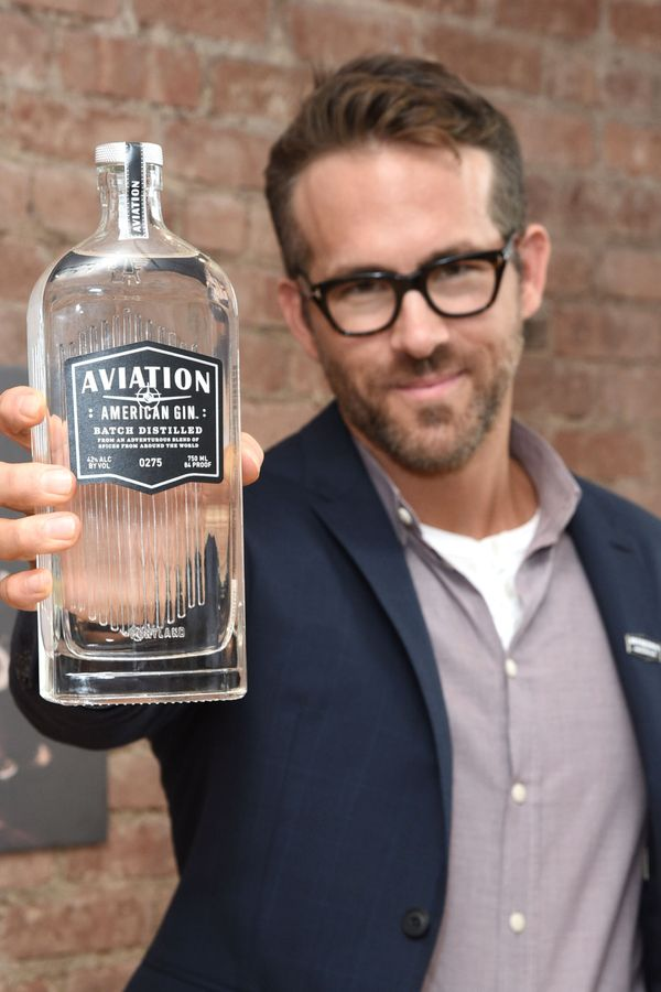 """Give Ryan Reynolds props for the slightly embarrassed look on his face as he holds up this bottle of <a href=""""http://www.avia"""