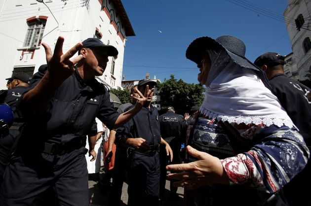 A demonstrator shouts at police officers during a protest opposing the election that Algeria's veteran...