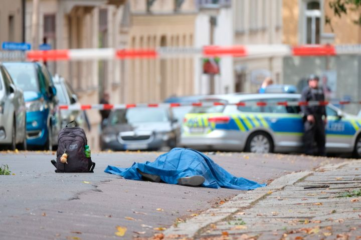 A person lies on a road in Halle, Germany, Wednesday, Oct. 9, 2019. A gunman fired several shots and at least two people were