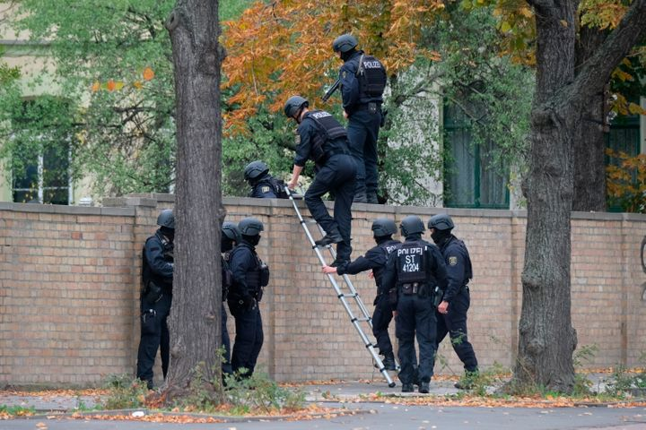 Police officers cross a wall at a crime scene in Halle, Germany, Wednesday, Oct. 9, 2019.