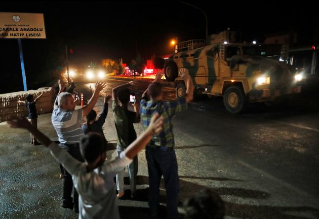 Local residents jeer and applaud as a convoy of Turkish forces vehicles and trucks carrying tanks and...