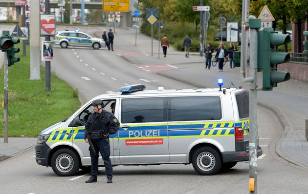 Police officers block a road in Halle, Germany, Wednesday, Oct. 9, 2019. One or more gunmen fired several...