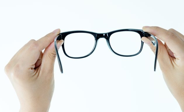 Woman hand holding eyeglasses on white