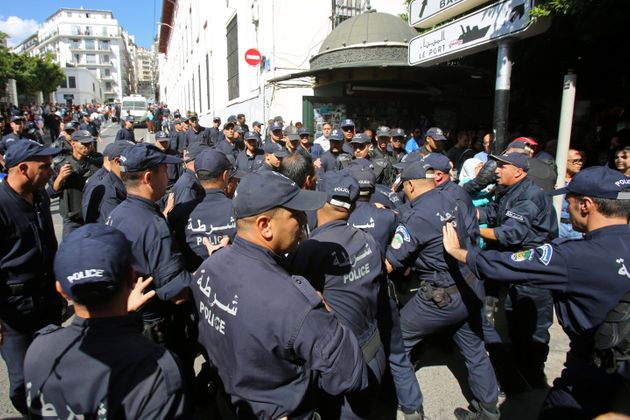 Police officers surround a demonstrator during a protest opposing the election that Algeria's veteran...