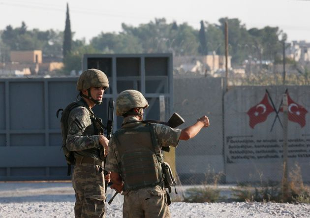 Shortly after the Turkish operation inside Syria had started, Turkish soldier stand at the border with...